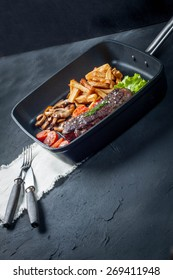 Fried steak with fries mushrooms and tomatoes.