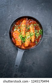 Fried suckling pig fillet in hot tomato chili sauce offered as top view in a modern design cast- iron pan with herbs