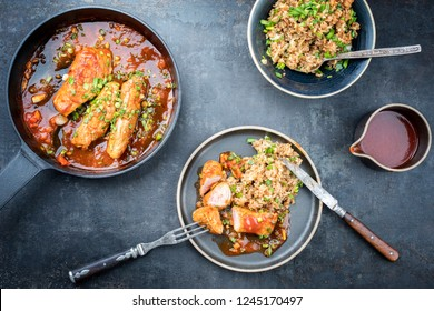 Fried suckling pig fillet with stir fried rice in hot tomato chili sauce offered as top view in a modern design cast- iron pan with herbs