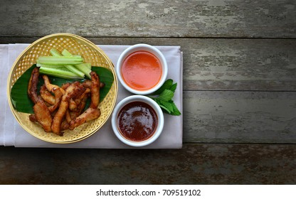Fried sun dried pork with herbs served with tomato and chilli sauce on wooden background. copy space