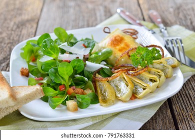 Fried Swabian meat ravioli (so called 'Maultaschen') served with corn salad with croutons, bacon and parmesan cheese