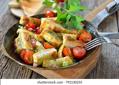 Fried Swabian meat ravioli (so called 'Maultaschen') with bacon and roasted cherry tomatoes served in an iron frying pan