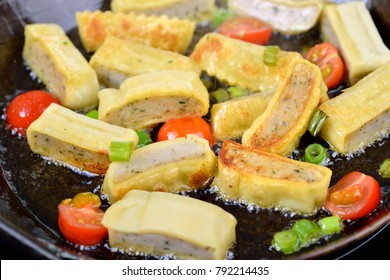 Fried Swabian meat ravioli (so called 'Maultaschen') cherry tomatoes and spring onions during frying in hot fat