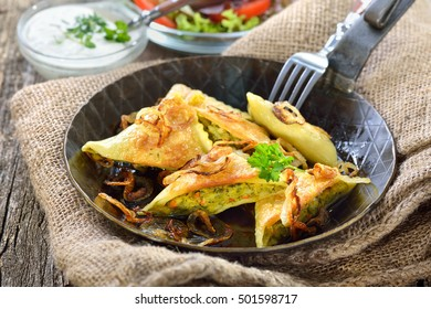 Fried Swabian ravioli (so called 'Maultaschen') with vegetable filling served with salad and creamy herb cheese