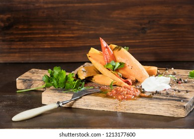 Fried sweet potato slices with pepers chilli, tomatoes and greenery on a dark wooden board background. Horizontal.