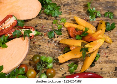 Fried sweet potato slices, raw yam with pepers chilli, tomatoes and greenery on a dark wooden board background. Horizontal.