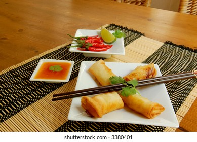 fried tasty spring-roll with garnish of red pepper, coriander and sweet chili sauce and chopsticks
