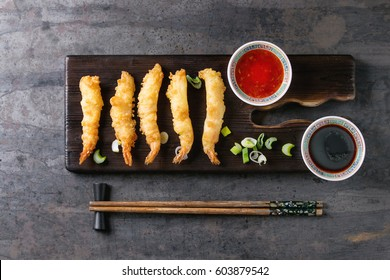 Fried tempura shrimps on lettuce salad with sauces. Served in traditional china plate with chopsticks on wood serving board and textile napkin over old metal background. Top view, space. Asian dinner