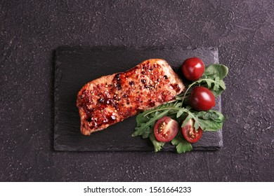 Fried teriyaki salmon with spices, sesame, green salad and tomatoes on stone plate, black textured background. Top view, flat lay, copy space.