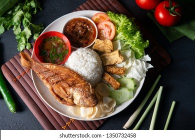 Fried tilapia fish and rice, popular traditional Malay or Indonesian local food. Flat lay top down overhead view.