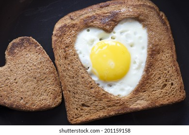 fried toast with egg in shape of heart on the black pan