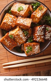 Fried tofu cheese with sesame seeds and garlic in a bowl close-up. vertical view from above