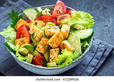 Fried Tofu Salad with Cucumbers, Tomatoes, Avocado and Sesame Seeds. Homemade asian vegetable and tofu salad in ceramic bowl on black stone background. Healthy asian diet vegan vegetarian salad food.