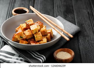 Fried tofu with sesame seeds and spices on black background.