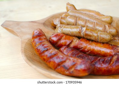 Fried Traditional and Vienna Sausage on a Wooden Plate