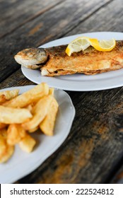 Fried Trout with lemon and french fries on different dishes, Sighnaghi , Georgian Restaurant, georgian cuisine