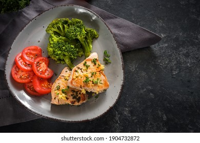 Fried tuna with broccoli and tomatoes on a gray plate and a dark rustic slate background, healthy meal for slimming with ketogenic or low carb diet, copy space, high angle view from above