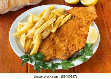 fried veal milanesa with potatoes on a plate