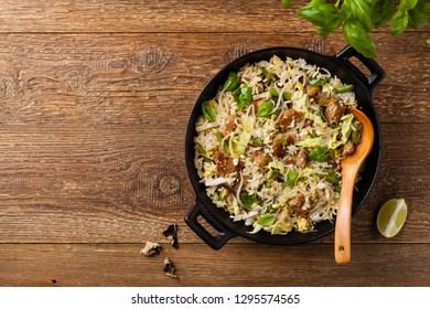Fried veal, with rice, Chinese cabbage and mushrooms. Sprinkled with sesame and soy sauce. Top view.