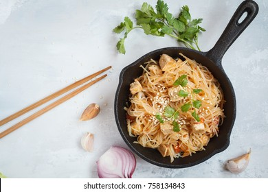 Fried vegan rice noodles with tofu and vegetables in cast iron frying pan, top view, light background. Healthy vegan food concept.