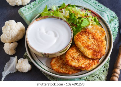 Fried vegetable patties on a plate. Homemade patties made of cauliflowers  and garnished with fresh green salad and yogurt sauce. Veggie lunch or dinner idea.