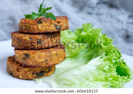 Fried vegetable patties on a plate. Yummy patties made of potatoes, green peas, carrot and green beans and garnished with fresh green onion. Veggie lunch or dinner idea.