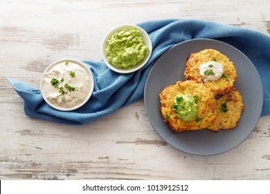 fried vegetable rosti from cauliflower with two dips on a blue plate and napkin on a bright wooden table with copy space, high angle view from above