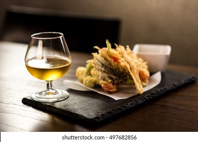 Fried vegetable tempura with wine glass on a black stone.