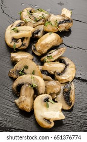 fried and warm mushroom slices and thyme on slate