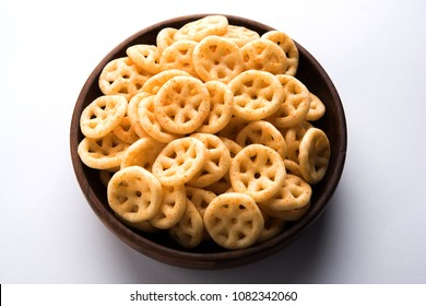 Fried wheel Snacks or Fryums served in a bowl or over moody background. selective focus