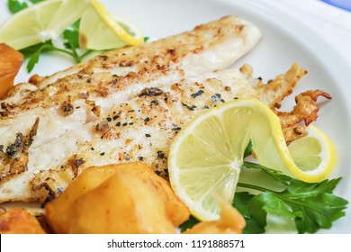 Fried white fish fillet garnished with roasted potatoes, lemon slices and parsley, Lebanese cuisine
