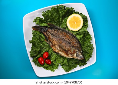 Fried whole tilapia fish on green leaves, shallow focus
