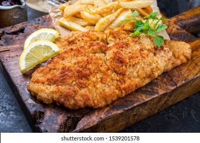 Fried Wiener schnitzel from veal topside with French fries and lemon slice as closeup on an old rustic cutting board
