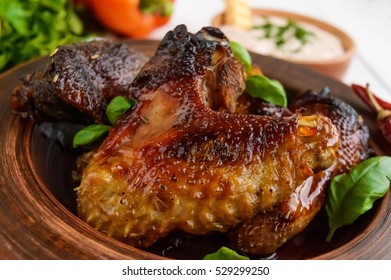 Fried wings (duck, chicken) in a honey glaze in a clay bowl on a light background.  Close up