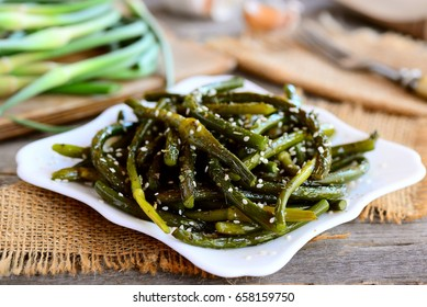 Fried young spring garlic with spices and sesame seeds on a white plate. Rustic style. Healthy vegetarian dish recipe. Closeup