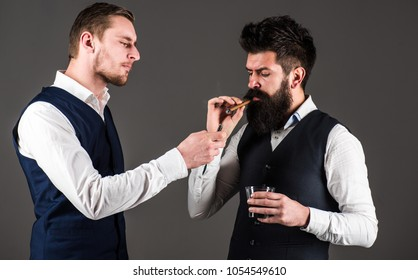 Friend, business partner, assistant helping man with beard light cigar. Luxury leisure concept. Business people on break with cigar and alcohol. Men in waistcoats looks sharp, grey background.