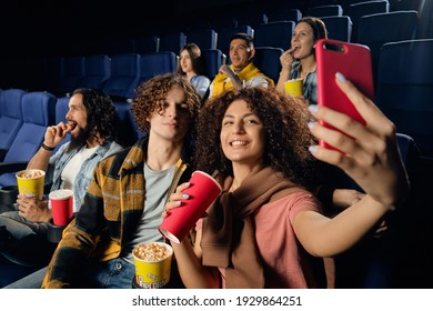 Friend in the cinema. Emotions of people watching amovie in a movie theater. Big group of young best friends, watching funny film at cinema, spending free time together, eating tasty popcorn.