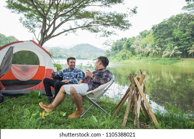 friend Enjoying Camping Holiday In Countryside near tent