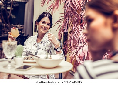 With a friend. Positive beautiful woman sitting in the restaurant while meeting there with her friend
