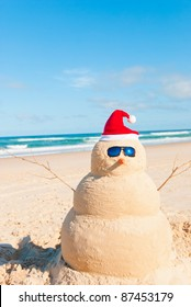 Snowman´s friend Sandman On holiday trip at the beach. He is wearing sunnies, santa hat and has a carrot as nose