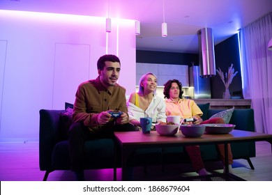 Friend of a young couple comes to their home to play games on gaming console on pleasant evening. Happy people playing video games at home. Home party.