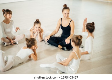friendly adult ballerina teacher sit on the floor with kids and have conversation, wearing tutu skirts, after practicing classic ballet dance