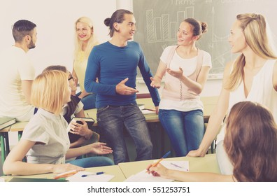 Friendly adult males and females chatting while sitting in the room