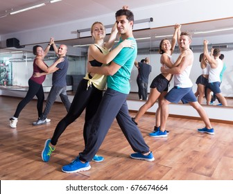 Friendly adults dancing bachata together in dance studio