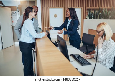 Friendly African American concierge giving two guests their check in information while working behind the reception counter of a hotel