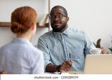 Friendly African American hr manager listening to candidate at job interview, good first impression, interested businessman consulting client, team leader having pleasant conversation with colleague