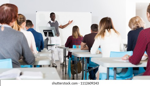 Friendly African American man lecturing to attentive adult students at auditorium