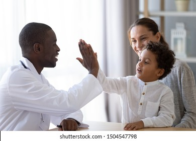 Friendly African American pediatrician doctor giving five to little boy patient, celebrating good medical checkup results, greeting little patient at consultation, children medical insurance