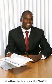 Friendly African businessman offering contract to sign.