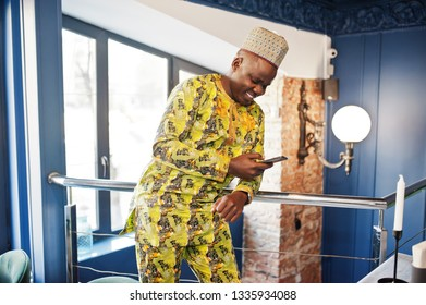 Friendly afro man in traditional yellow clothes with cap at restaurant near the handrail look at mobile phone.